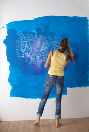 housepainter: Beautiful young woman doing wall painting, standing near ladder Stock Photo