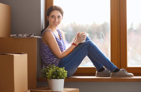 windowsill: Girl sitting on windowsill at new home. Stock Photo