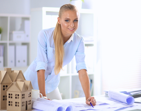 female architect: Portrait of female architect with blueprints at desk in office.