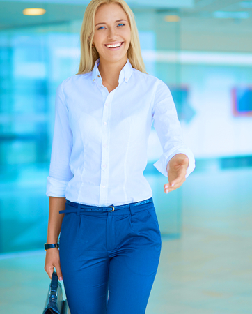 businesswoman suit: Young business woman ready to handshake standing in office . Stock Photo