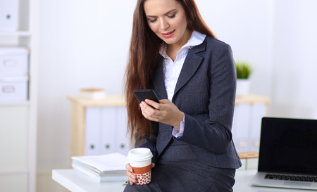 sending: Businesswoman sending message with smartphone sitting . Stock Photo