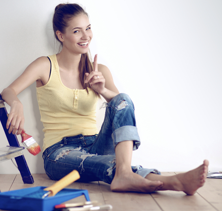 housepainter: Portrait of female painter sitting on floor after painting.