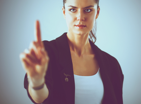 press button: Woman touching an imaginary screen with her finger .