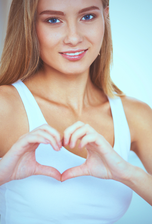 courting: Beautiful woman showing heart shape on her hand