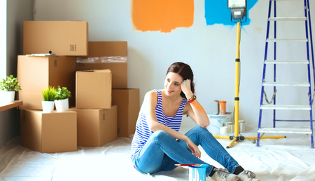 renovating: Young woman portrait while painting new apartment .