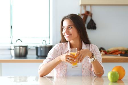 mujer sentada: Mujer joven que se sienta cerca del escritorio en la cocina.