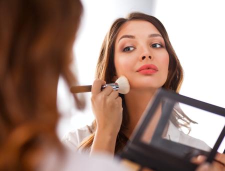 woman mirror: Young beautiful woman making make-up near mirror .