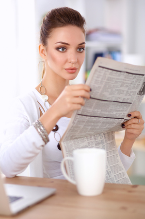 at her desk: Cute businesswoman holding newspaper sitting at her desk in office .