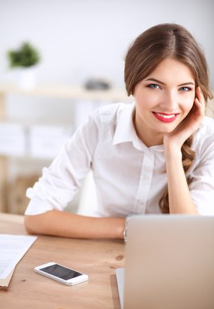 gleeful: Attractive businesswoman sitting in the office, isolated