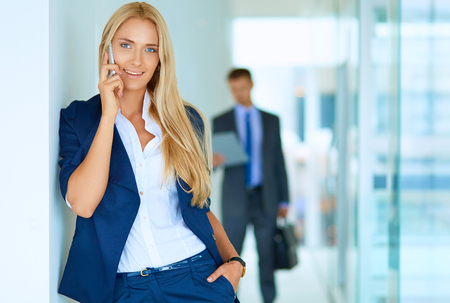 phon: Businesswoman standing against office window talking on mobile phone .