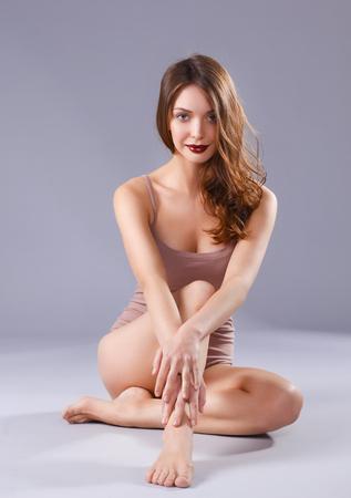 Beautiful barefoot woman sitting on the floor. Stock Photo