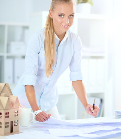 female architect: Portrait of female architect with blueprints at desk in office .