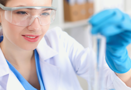 vials: Woman researcher is surrounded by medical vials and flasks Stock Photo