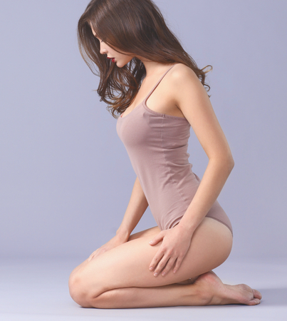 Beautiful barefoot woman sitting on the floor. Imagens