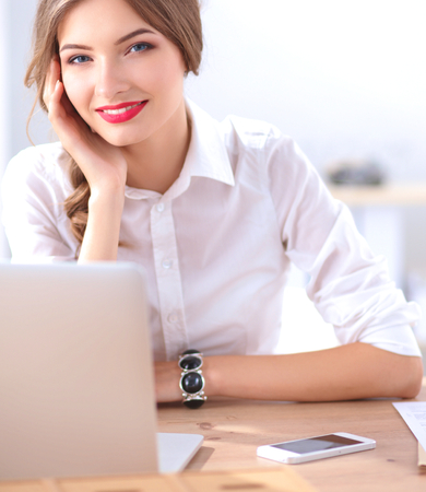 glee: Attractive businesswoman sitting in the office, isolated