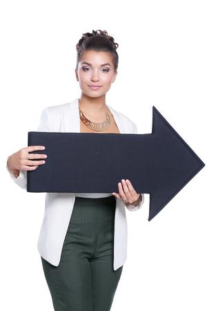Bella giovane donna d'affari in possesso di un frecce nere, su uno sfondo bianco Archivio Fotografico