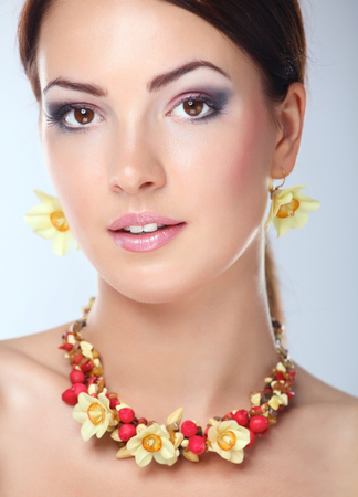 Portrait of young beautiful brunette woman in beads .