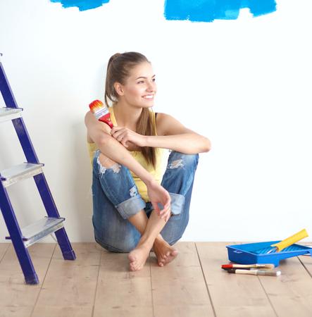 Porträt der Malerin, die nach dem Malen auf dem Boden sitzt.