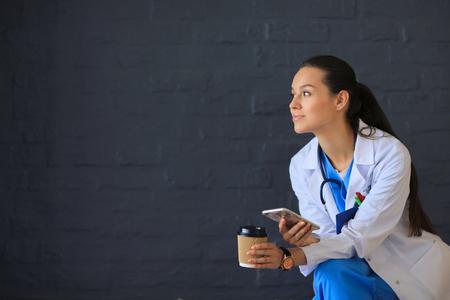 女性医師の携帯電話で座って、コーヒーを飲みながら