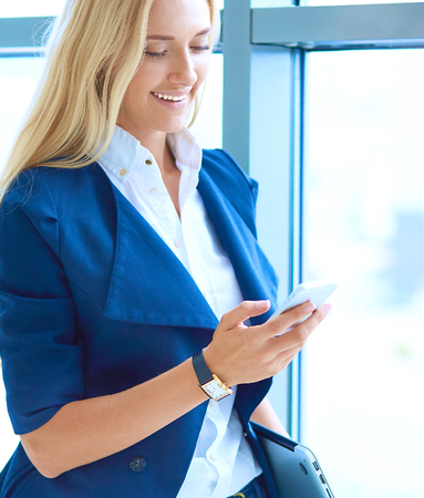 phon: Businesswoman standing against office window send a message on mobile phone Stock Photo