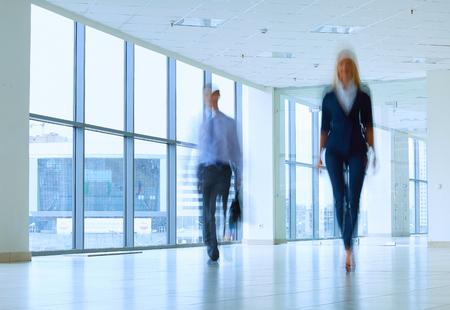 businesslike: Businesspeople walking in the corridor of an business center.