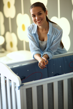 bed skirt: Young woman standing near childrens cot.