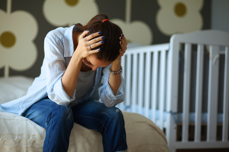 bed skirt: Young tired woman sitting on the bed near childrens cot. Stock Photo
