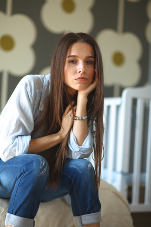 cot: Young tired woman sitting on the bed near childrens cot. Stock Photo