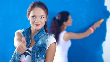 Two Beautiful young woman doing wall painting Stock Photo