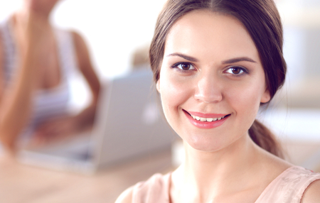 Attractive businesswoman sitting on desk in the office.