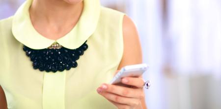 Pretty diseñador de moda que trabaja en oficina usando el teléfono móvil, aislado