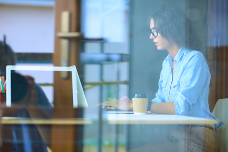 stockphoto: Young woman sitting at office table with laptop,view through window