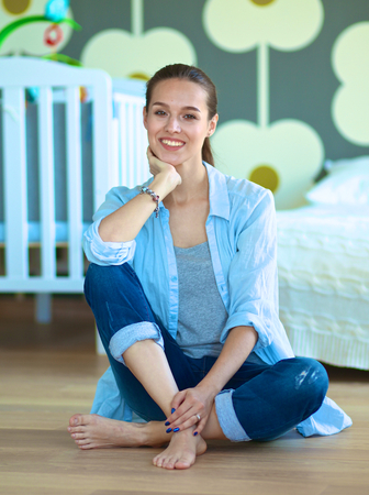 bed skirt: Young woman sitting on the floor near childrens cot.