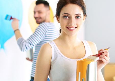 Portrait of happy smiling young couple painting interior wall of new house Stock Photo
