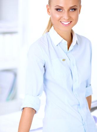 principal: Atractiva joven empresaria de pie cerca del escritorio en la oficina.