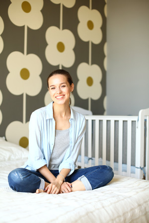 cot: Young woman sitting on the bed near childrens cot. Stock Photo