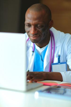 デスクでのラップトップに取り組んで若いアフリカの医師 写真素材