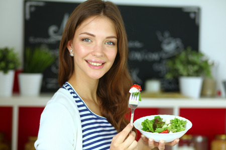 domicile: Young woman eating salad and holding a mixed salad