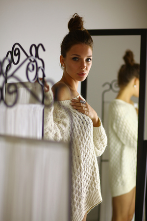 red cardigan: Portrait of a cute woman in sweater at home