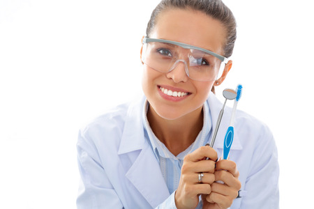 hand tool: Beautiful female dentist doctor holding and showing a toothbrush isolated on a white background Stock Photo