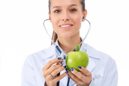 dietetics: Medical doctor woman examining apple with stethoscope