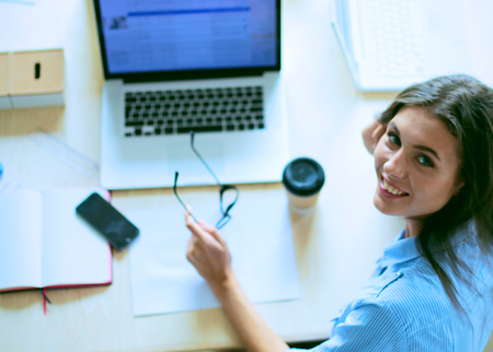 Young woman sitting at office table with laptop