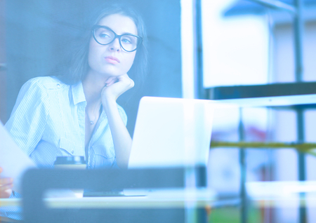 Young woman sitting at office table with laptop,view through window