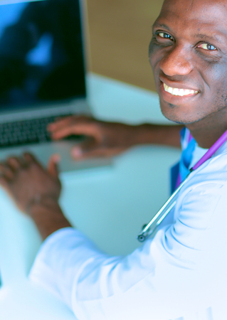 medical man: Young african doctor working on laptop at desk