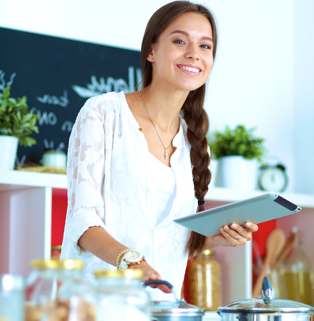 caucasian appearance: Young woman using a tablet computer to cook in her kitchen .