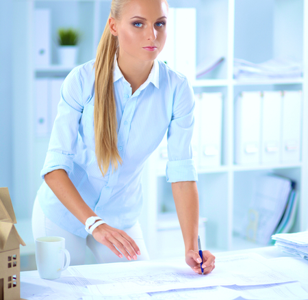 female architect: Portrait of female architect with blueprints at desk in office