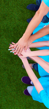 joining: People joining their hands  on green grass . Stock Photo