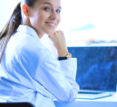medical professional: Beautiful young smiling female doctor sitting at the desk