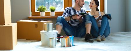 Attractive couple assis sur le plancher de la maison en regardant jurnal et souriant à l'autre. Banque d'images - 61832556