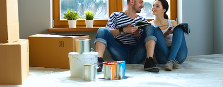 Coppie attraenti seduta sul pavimento a casa guardando Jurnal e sorridente a vicenda. Archivio Fotografico